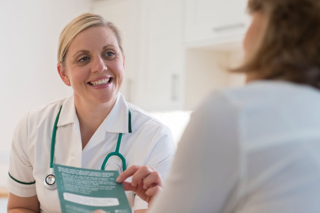 Nurse Discussing Leaflet With Female Patient